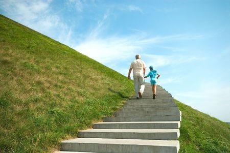 grandchild: The grandfather and grandson walk in park