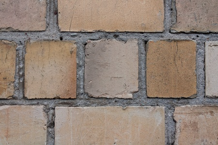 beige and brown brick wall close-up with scratches photo