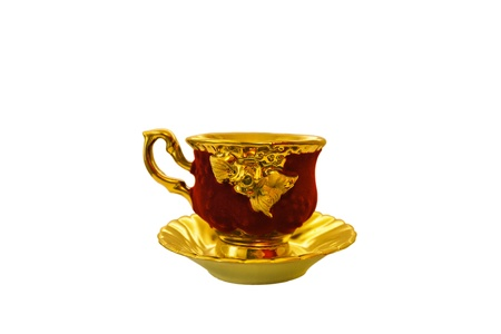 gold-plated cup and saucer isolated on white background Editorial