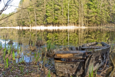 Destroyed the old boat on the lake in the woods Stock Photo - 14469494
