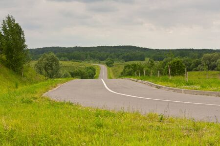 Country road in the hills and fields Stock Photo - 14469499