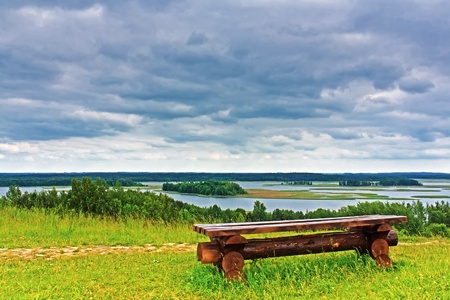Wooden bench on the banks of the Braslav lakes and stormy sky photo