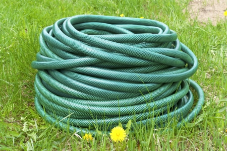 Garden hose for water on the green grass