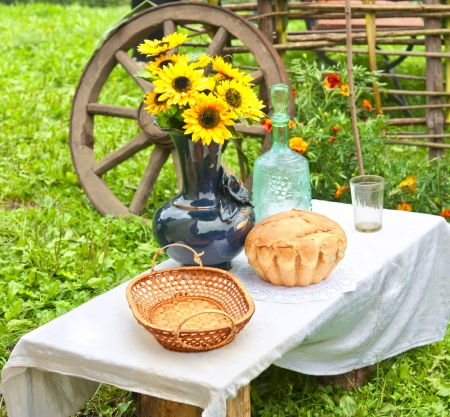 Fresh bread on the table and a bunch of flowers photo