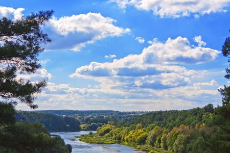Forest river and a beautiful blue sky with clouds landscape photo