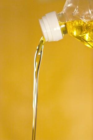 aceite de cocina: El aceite de girasol se vierte de una botella en un fondo amarillo