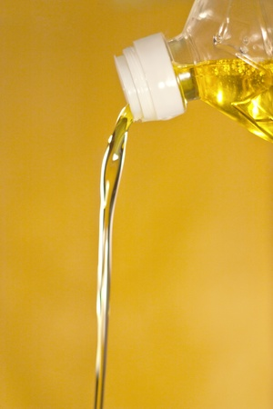 Sunflower oil is poured from a bottle on a yellow background