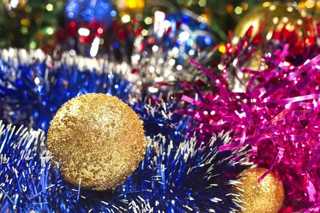 Golden Christmas ball and colored tinsel in the background photo