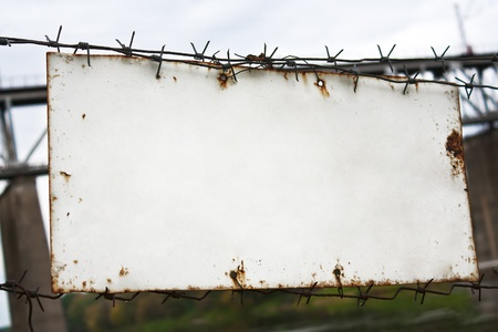 Old white plate on a barbed wire fence photo