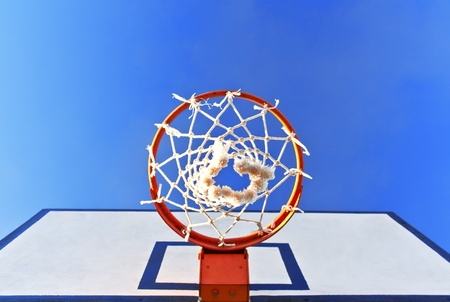 the height of a rim: Bottom view of a basketball hoop against a blue sky Stock Photo