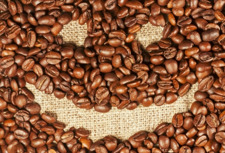 horisontal: Cheerful smiley painted on roasted coffee beans, horisontal background