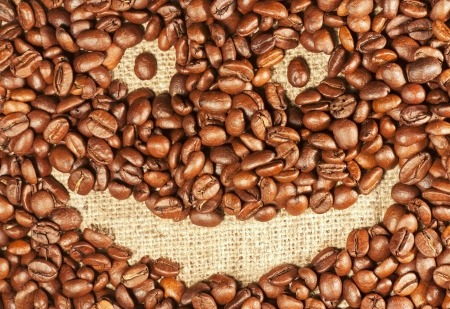 Roasted coffee beans in the form of a smiling face background photo