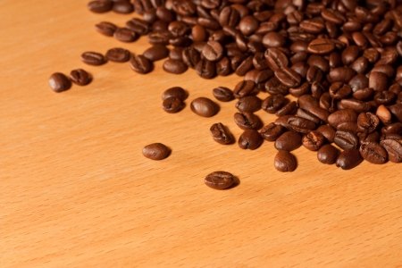 A pile of coffee beans on a wooden table background photo