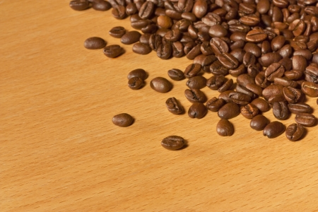 A lot of roasted coffee beans on a wooden table photo