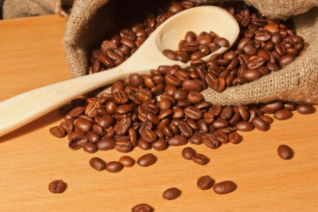 Coffee beans and a wooden spoon in a sack on the table photo