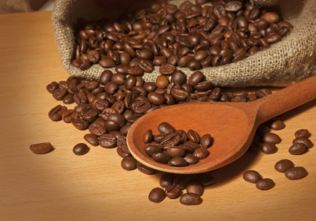 Roasted coffee beans in a bag with a wooden spoon background photo