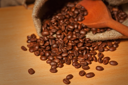 Pile of coffee beans in a sack and wooden spoon background