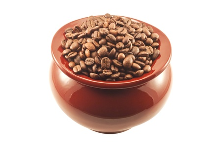 Coffee beans in a brown clay pot, top view isolated