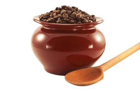 Coffee beans in a brown clay pot with a wooden spoon isolated on white background photo