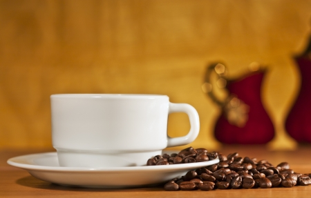 White coffee cup and saucer with coffee beans on a yellow background with a coffee pot