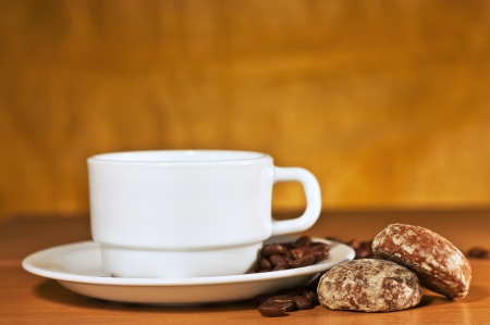 White cup of coffee on a saucer and cakes on a yellow background photo
