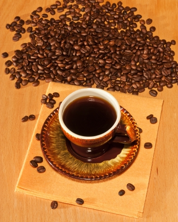 Black coffee cup and saucer on a napkin is on the table and coffee beans in the background Stock Photo