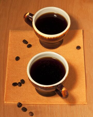 Two black coffee cup on a yellow napkin