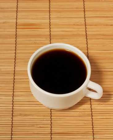 One white cup of coffee on a wooden table cloth Stock Photo