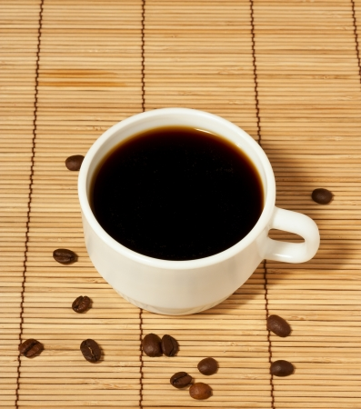 One white coffee cup with coffee beans on a wooden table cloth Stock Photo