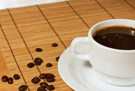 White coffee cup and saucer with coffee beans is on the wicker table cloth Stock Photo