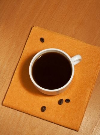 One white coffee cup on a yellow napkin, top view photo