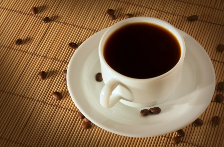 White cup of coffee with a plate on a straw cloth photo