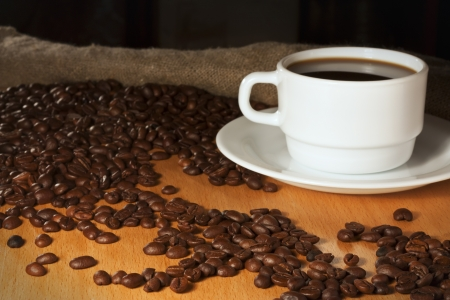 White cup of coffee with coffee beans and burlap in the background