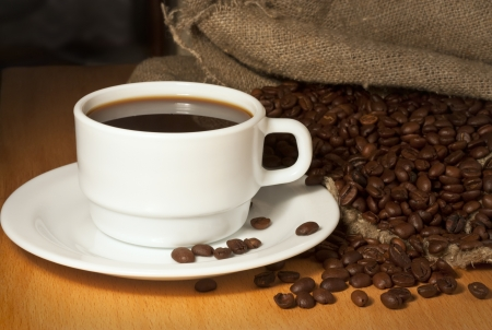White cup of coffee on a saucer with a burlap sack and roasted coffee beans Stock Photo - 17292306