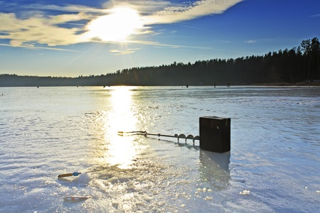 Winter fishing on the lake and fishermen on the ice in the background Stock Photo - 17292313