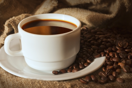 White cup of coffee on sacking and coffee beans still life Stock Photo - 17471642