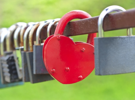 Red heart-shaped lock between the other locks