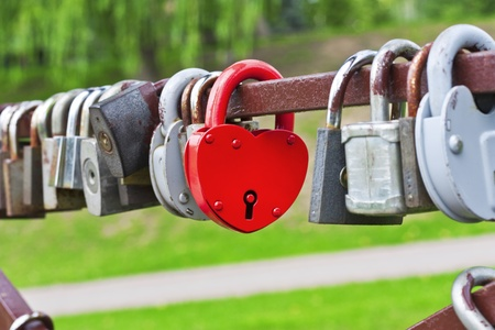 Red heart-shaped padlock between the other padlocks photo