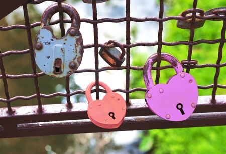 Red and pink heart-shaped padlocks between the other padlocks photo