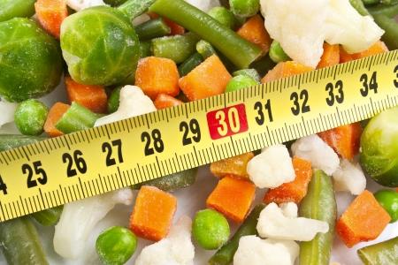 細かく刻んだ新鮮な健康野菜にんじん、キャベツ、エンドウ豆、豆、採寸テープをクローズ アップ