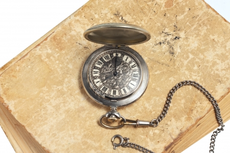 Pocket watch lying on old book isolated photo