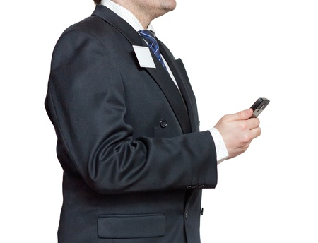 Businessman in a black suit with a badge and mobile phone isolated on white background photo