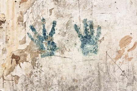 Texture of the old worn beige wall with handprint photo