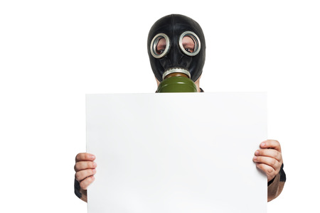 The man in a gas mask holding a blank sheet of paper isolated photo
