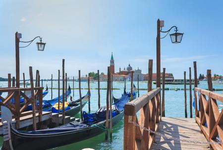 Gondolas stand at the pier in Venice photo