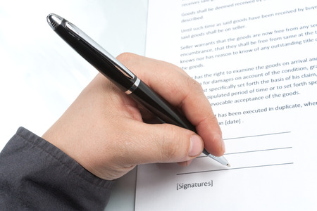 Businessman holding a pen and signs the contract
