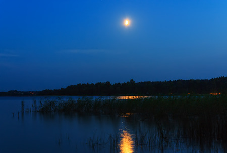 braslav: The moon in the night sky on the lake