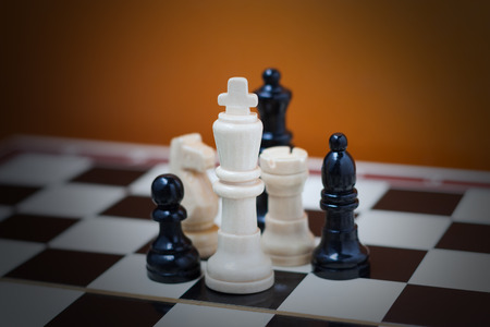 Group of chess pieces on a chess board with vignette photo