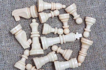 sacking: Heap of white chess pieces on sacking Stock Photo