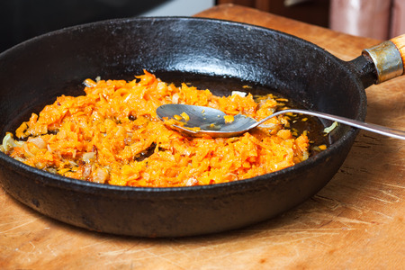 Braised carrots and onions in a frying pan photo